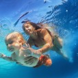 In blue pool young mother swimming with happy baby son - dive underwater with cheerful boy. Healthy family lifestyle and children water sports activity with parents during summer vacation with child