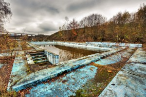 Abandoned overgrown outdoor swimming pool